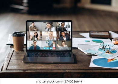 Video call. Video conference by laptop. Online business meeting. On the laptop screen, people who gathered in a video conference to work on-line, near stands a cup of coffee and different graphs