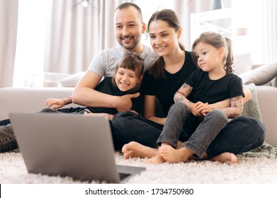Video call. Happy cheerful family. Young parents and their two amazing daughters communicate via video conference with grandparents sitting at home on the floor  in stylish casual wear