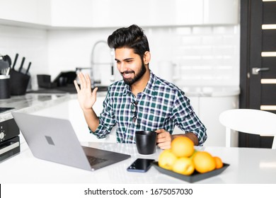 Video call. Positive joyful nice man looking at the laptop screen and waving his hand while greeting his friend