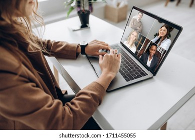 Video call. Remote work. A girl work from home. She communicate via video communication with colleagues using laptop