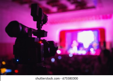 Video camera at the concert. Capture a video. Violet light in the hall. Creative work. To shoot a movie. Video equipment