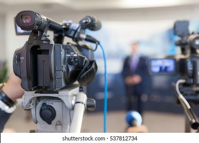 Video camera in focus, blurred spokesman in background. News conference.