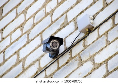video camera with illumination is hanging on the wall. Wall of white brick and a video camera with wires