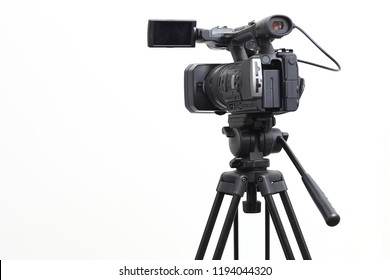 The video camera with the microphone is standing on the tripod isolated on white, in concept of technology, modern, entertainment. - Shutterstock ID 1194044320
