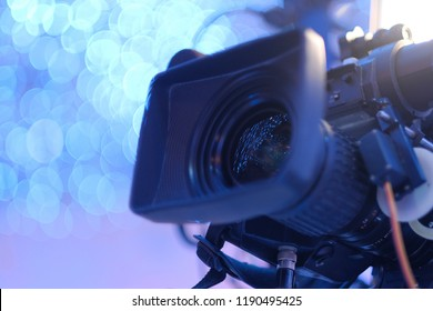 Video camera on the crane conducts shooting of a wedding in the hall of celebrations against the background of multi-colored fires.Close-up.