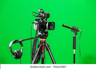 Video camera on a tripod, headphones and a directional microphone on a green background. The chroma key. Green screen.