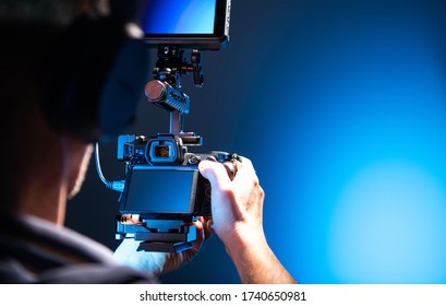 Video Camera Operator with Modern Digital SLR Camera in Hands and Additional Large Display. Videography Theme. Dark Blue Light in a Studio.