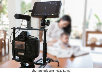 Video camera set on foreground and mom with baby  model playing on the table inside house.