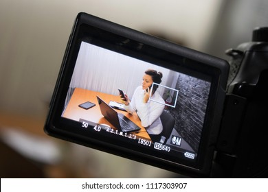 Video camera shoots a young businesswoman sitting at a table in front of a laptop and making a phone call
