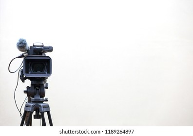 The video camera is standing on the tripod isolated on white.