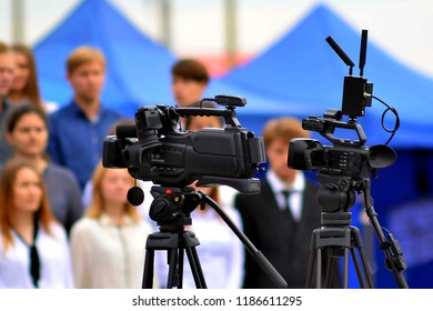 a video camera stands on a tripod at a solemn event