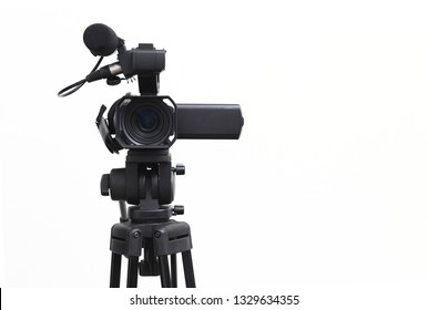 The video camera with the tripod isolated on white background.