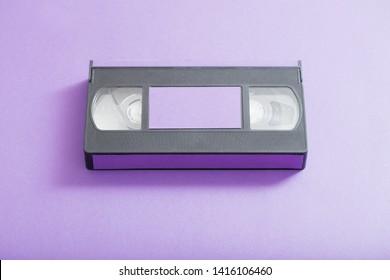 Video cassette on violet background. Retro concept