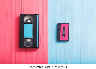 Video cassette and tape cassette on pink and blue wooden background background. Retro concept
