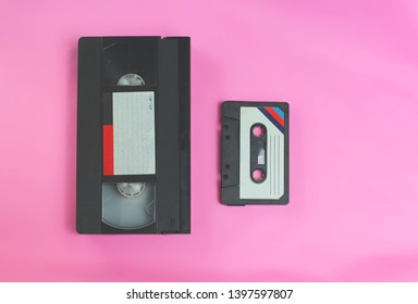 Video cassette vhs and audio cassette tape retro vintage spirit of 1970s, 1980s, 1990s style on pink background with selective focus