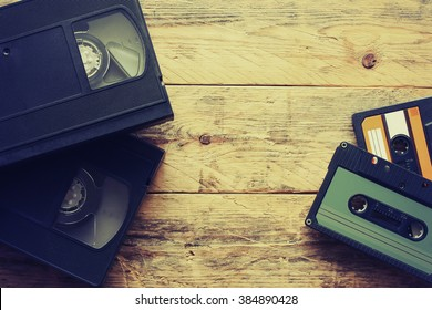 video cassettes and audio cassettes on a wooden table, retro style