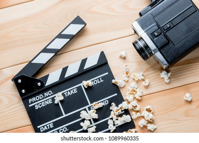 video clapper, retro video camera and salted popcorn top view on wooden boards