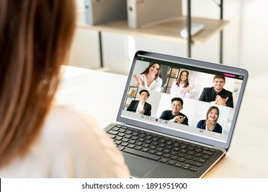 Video conference. Business webinar. Distance teamwork. Pandemic WFH. Supportive diverse multiracial corporate team encouraging colleague on laptop at light modern home office workplace.