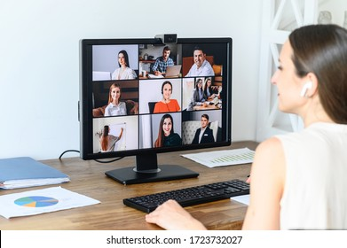 Video conference with colleagues, coworkers. A young businesswoman using application on pc in office for online conversation with coworkers. Back view