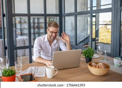 Video conference. Young handsome man in white shirt greeting his colleague online
