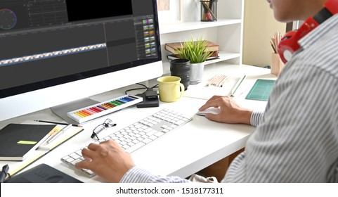 Video editing with computer professional editor adding colour grading footage.