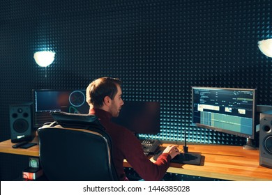 Video editing. Professional editor adding special sound effects. Back view of young man watching graphs on monitors. Copy space on gray wall