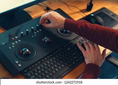 Video editor hands adjusting color or sound on working console machine in the post production stage.