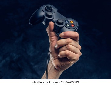 Video game console controller in gamer hand against a dark wall