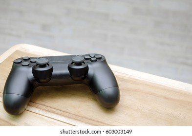 Video game controller on wooden desk with brick  wall background, copy space for text, color tone effect.