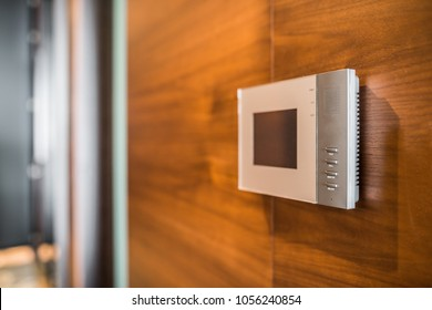 Video intercom display on wooden wall near the entrance door