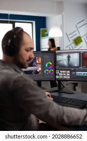 Video maker with headset working with footage and sound on pc with two displays, taking notes while editing customer creative video. Man editor processing film montage in startup agency office.