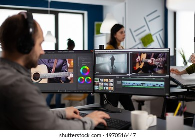 Video maker listening music at headphones editing movie using post production software working in creative agency office. Videographer processing audio film montage on computer in multimedia company