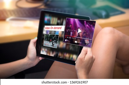 Video on demand,online streaming video concept.back-view of Woman watching onlive video streaming via tablet