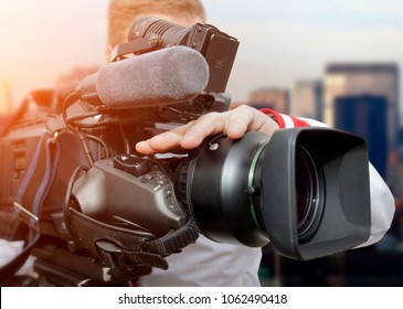 Video operator with camcorders on tripods recording video at an event
