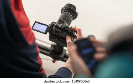 Video operator shoots music video in studio.Professional videographer shooting footage on white background.Media production in process