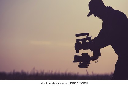 Video Production Concept. Silhouette of Gimbal Camera Operator. Picture Stabilization Device.
