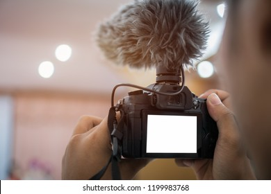 Video or professional digital mirrorless on tripod for camera recording with microphone taking photograp in wedding convention hall in live streaming event, seminar production equipment.