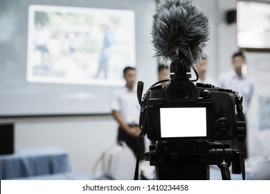Video or professional digital mirrorless on tripod for camera recording with microphone taking photograp in students group presentation on front classroom for live streaming event production