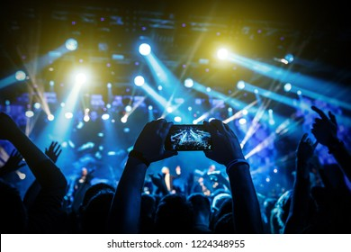 Video recording of concert by smartphone phone. Blue conceptual background of show.