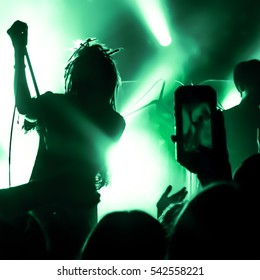 Video recording of the concert on the phone a smartphone. Reggae colors.