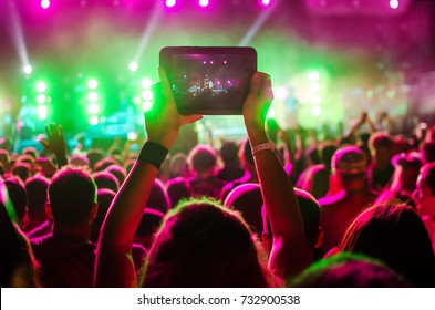 Video recording of the concert on the phone a smartphone. Reggae colors. Blue conceptual background of the youth party.