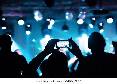 Video recording of the concert on the smartphone phone of the Beach or club party. Conceptual background of the youth party. blurred