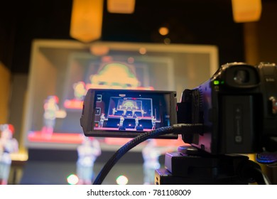 Video shooting with video camera recording of Thai dancing event show on stage, movie camera filming production concept