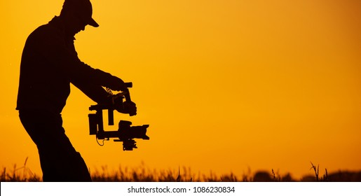 Video Stabilizer Operator. Taking Video Shoots Using DSLR Gimbal Equipment. Sunset Silhouette Concept.