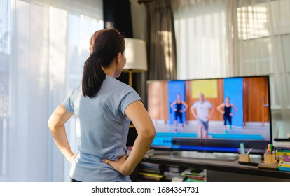 Video streaming Stay home.home fitness workout class live streaming online.Asian woman doing strength training cardio aerobic dance exercises watching videos on a smart tv in the living room at home. - Shutterstock ID 1684364731