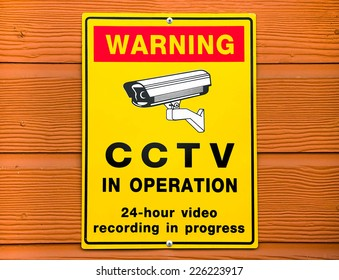 Video surveillance sign. CCTV Camera on wood background