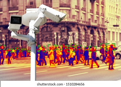 Video surveillance and technology. Video surveillance camera on the background of people walking on a pedestrian crossing. Face recognition effect. Blur.