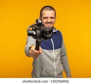 Videographer or blogger man pointing camera with gimbal