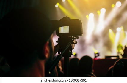 Videographer with camera filming music concert on video at night