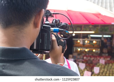 Videographer or Cameraman Shooting interview Footage outdoor on Location with handheld Equipment camera